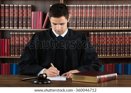Young male judge making legal documents at desk against bookshelf in courtroom - stock photo