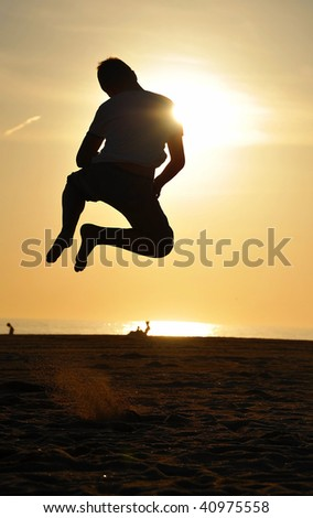 Young male jumping on a beach with an evening sun - stock photo