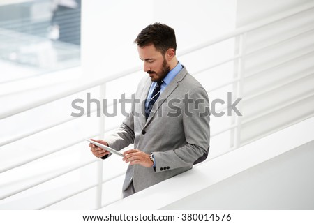 Young male lawyer searching information on touch pad during work break after business meeting with client, successful man employer checking e-mail via digital tablet while standing in office interior - stock photo