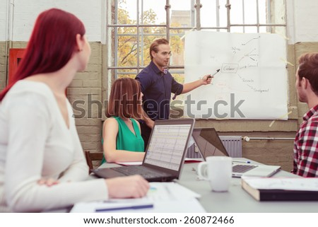 Young Male Leader Discussing Project Plans at the White Board to his Friends Sitting on the Table with Laptops. - stock photo