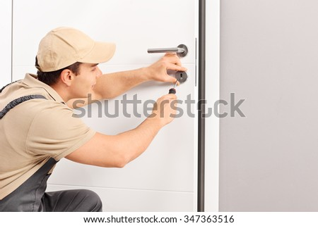 Young male locksmith installing a lock on a new door with a screwdriver  - stock photo