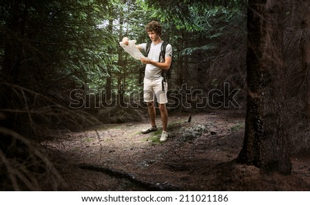 Young male looking at map and planning trip or get lost in the dark woods - stock photo