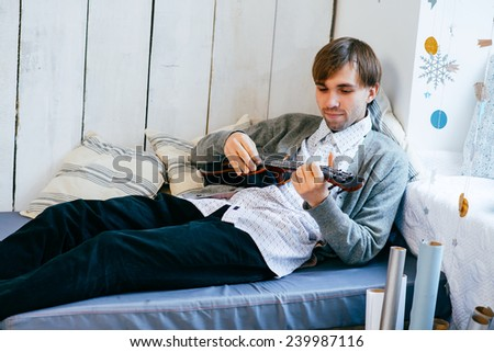 young male lying on a modern couch and playing a guitar - stock photo