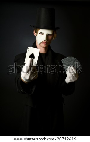 Young male magician playing with cards - stock photo