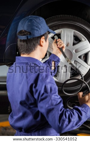 Young male mechanic filling air in car tire at auto repair shop - stock photo