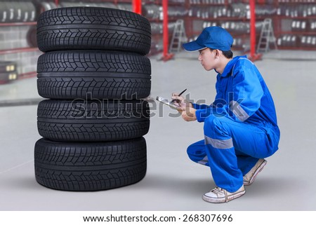 Young male mechanic working in the workshop and inspecting the tires texture - stock photo
