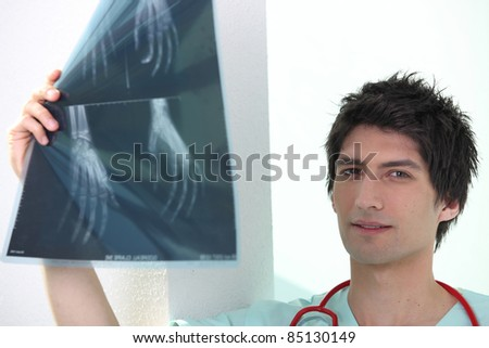 Young male medic examining Xrays of hands - stock photo