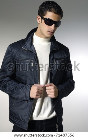 young Male model and sunglasses on light background - stock photo
