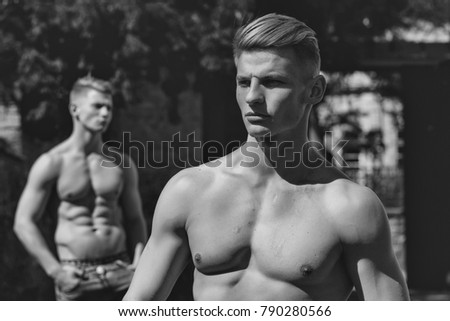 Young male model bodybuilder with serious look while muscular twin brother with bare chest poses outdoor on blurred background