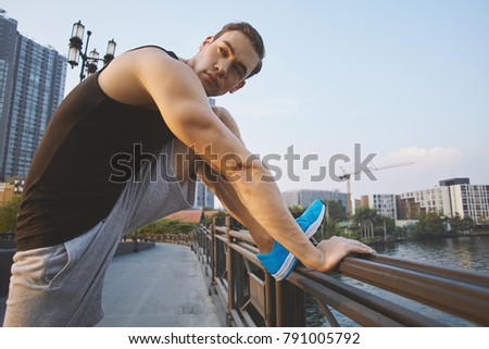 Young male model doing exercises at the outdoor in the city are