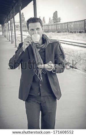 young male model drinking coffee at train station
