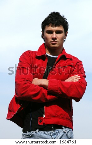 Young male model in a red jacket waiting for somebody - stock photo