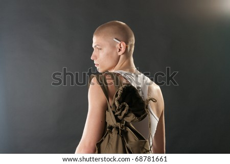 Young male model in military outfit with military style backpack as if leaving for service in studio on black - stock photo