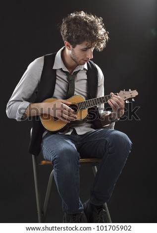 Young male musician sits and plays a ukulele. Backlighting, dark background, copy space, vertical.
