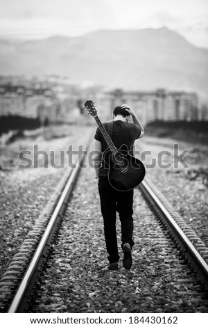 Young male musician walking with his acustic guitar. - stock photo