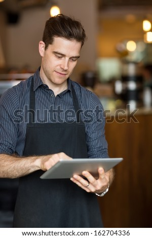 Young male owner using digital tablet while standing in shop - stock photo