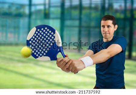 young male paddle tennis player standing and swatting the ball - stock photo