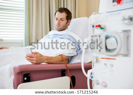 Young male patient using mobilephone at dialysis center, waiting for treatment - stock photo