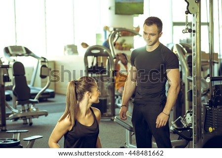 Young male personal fitness trainer talks to his female client and giving her advices for motivation. - stock photo