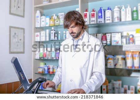 young male pharmacist using the computer in the pharmacy standing - stock photo