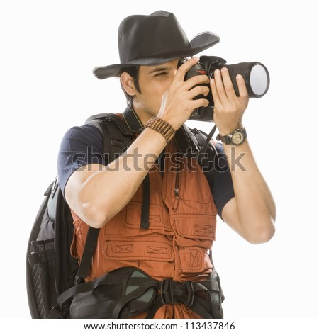 Young male photographer photographing with a digital camera