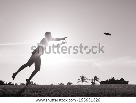 Young male playing frisbee in the park - stock photo