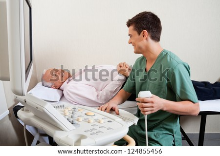 Young male radiologic technician smiling while looking at senior patient - stock photo