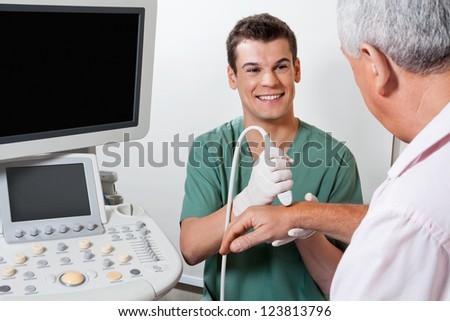 Young male radiologic technician smiling while scanning male patient's hand at clinic - stock photo