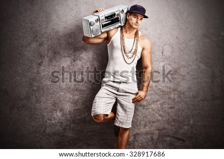 Young male rapper in hip-hop outfit listening to music from a ghetto blaster and leaning against a rusty gray concrete wall - stock photo