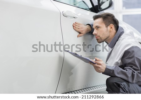 Young male repair worker examining car in automobile repair shop - stock photo