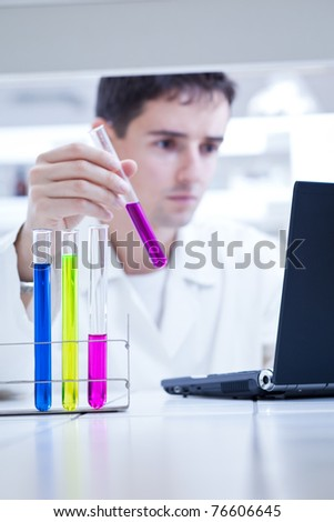 young, male researcher carrying out scientific research in a lab (color toned image; shallow DOF) - stock photo