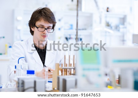 young, male researcher/chemistry student carrying out scientific research in a lab (shallow DOF; color toned image) - stock photo