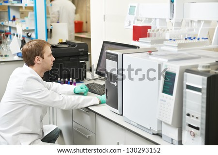 young male researcher works at computer scientific analysing data out scientific test in chemistry laboratory - stock photo
