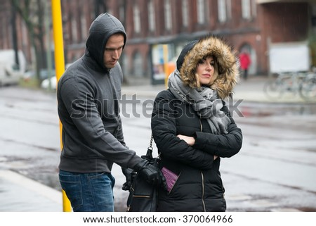 Young male robber stealing clutch from woman's jacket on street during winter - stock photo