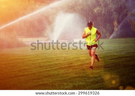 Young male runner jogging over green grass in the park with copy space area for your text message or content, healthy athlete performs physical exercises outdoors at summer afternoon, filtered image - stock photo