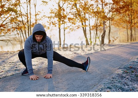 Young male runner stretching his legs after running workout - stock photo
