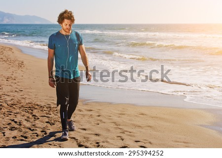 Young male runner walking along beautiful seashore while listening to music with headphones and taking break after active physical training outdoors, copy space for text message to advertising content - stock photo