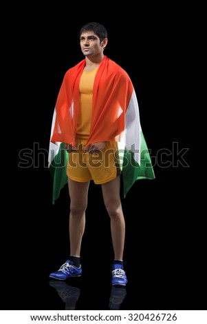 Young male runner with Indian flag standing against black background - stock photo
