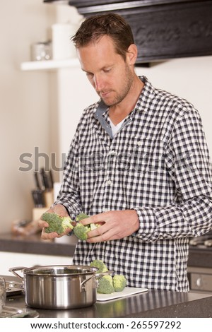 Young male 30s cook cooking in his own kitchen at home preparing healthy vegetables - stock photo
