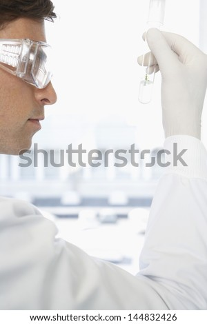 Young male scientist examining solution in test tube at laboratory - stock photo