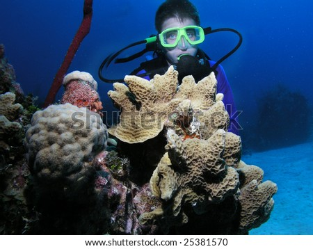 Young male scuba diver poses behind a coral head. - stock photo