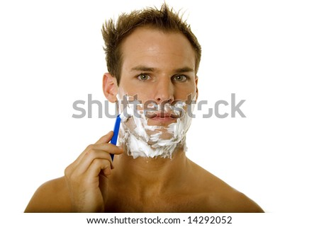Young male shaving his beard with razor