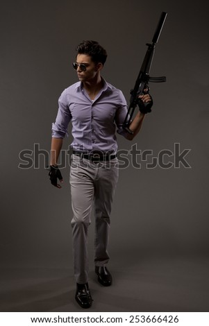 Young male shooter or contractor in casual attire with an automatic rifle on grey background.
