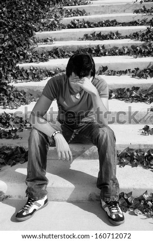 Young male sitting  on some park stairs in  a desperate attitude - stock photo