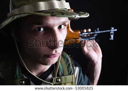 Young male soldier with kalashnikov rifle on shoulder.