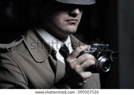 Young male spy agent wearing a hat, coat and a tie, holding rangefinder Leica film camera. Eyes hidden in the shadow. - stock photo