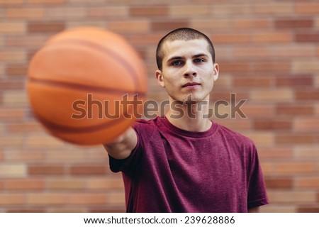 young male student holding basketball, no smile, horizontal - stock photo