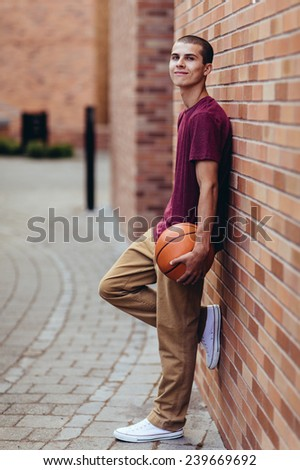 young male student holding basketball, slight smile, leaning against brick wall - stock photo