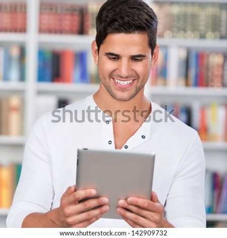 Young male student holding digital tablet in library - stock photo
