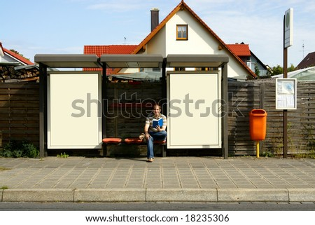 young male student sitting at bus stop with blank billboards - stock photo